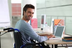 smiling man in a wheelchair on his computer