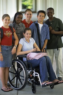 young group standing by a girl in a wheelchair