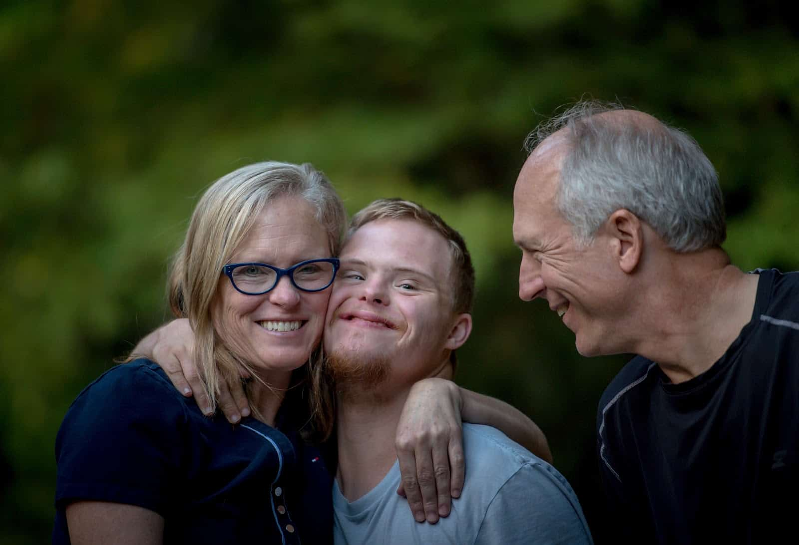boy with disability smiling with his family